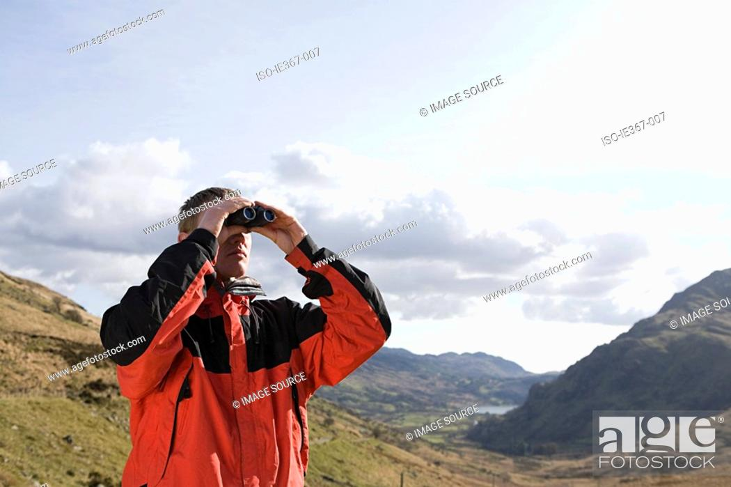 Stock Photo: A man looking through binoculars.