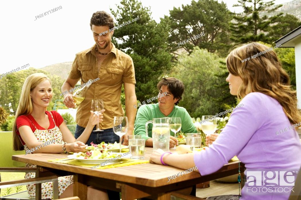 Stock Photo: 2 young smiling couples sitting at garden table, man pouring wine.