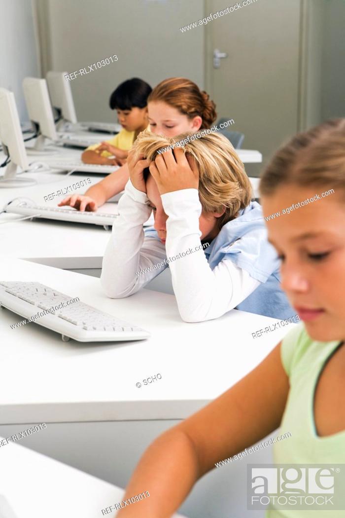Stock Photo: Group of school children 10-13 using computers in classroom.