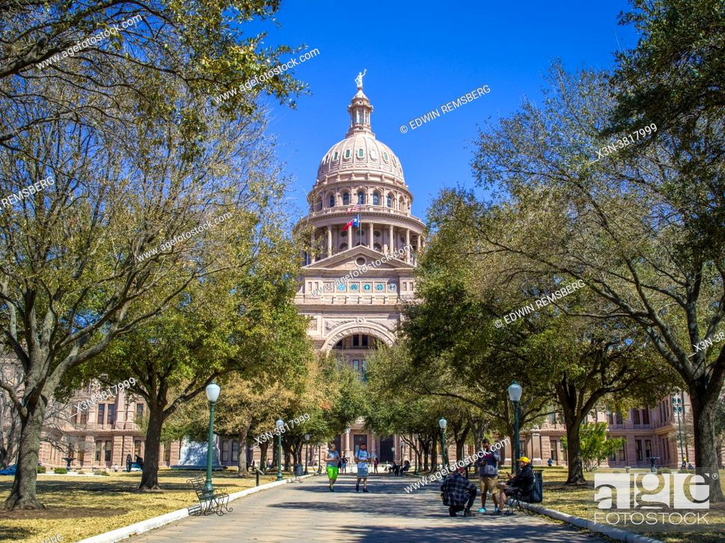 Stock Photo: View down sidewalk towards pink State Capitol building in Austin, TX.
