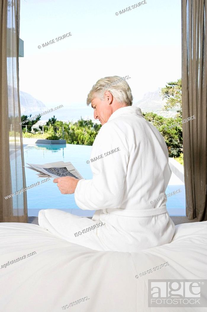 Stock Photo: Middle aged man in robe sitting on bed reading newspaper with view out to swimming pool.