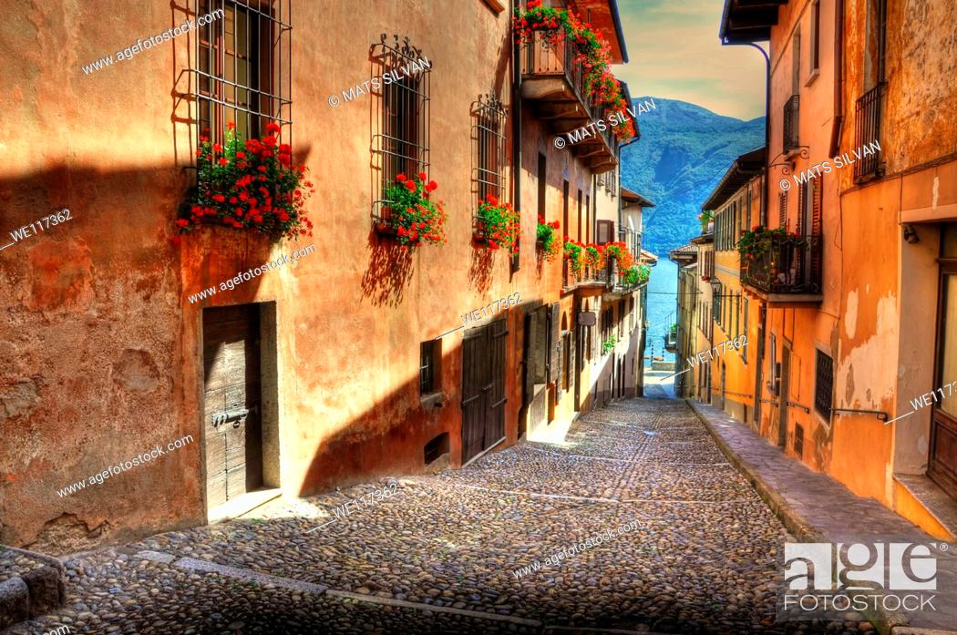 Stock Photo: Tight alley with sunlight and old houses with red flowers and lake with mountain.