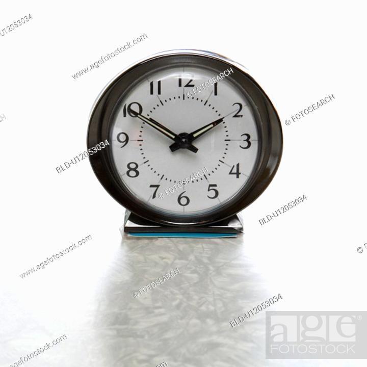Stock Photo: Still life of round vintage alarm clock on table.