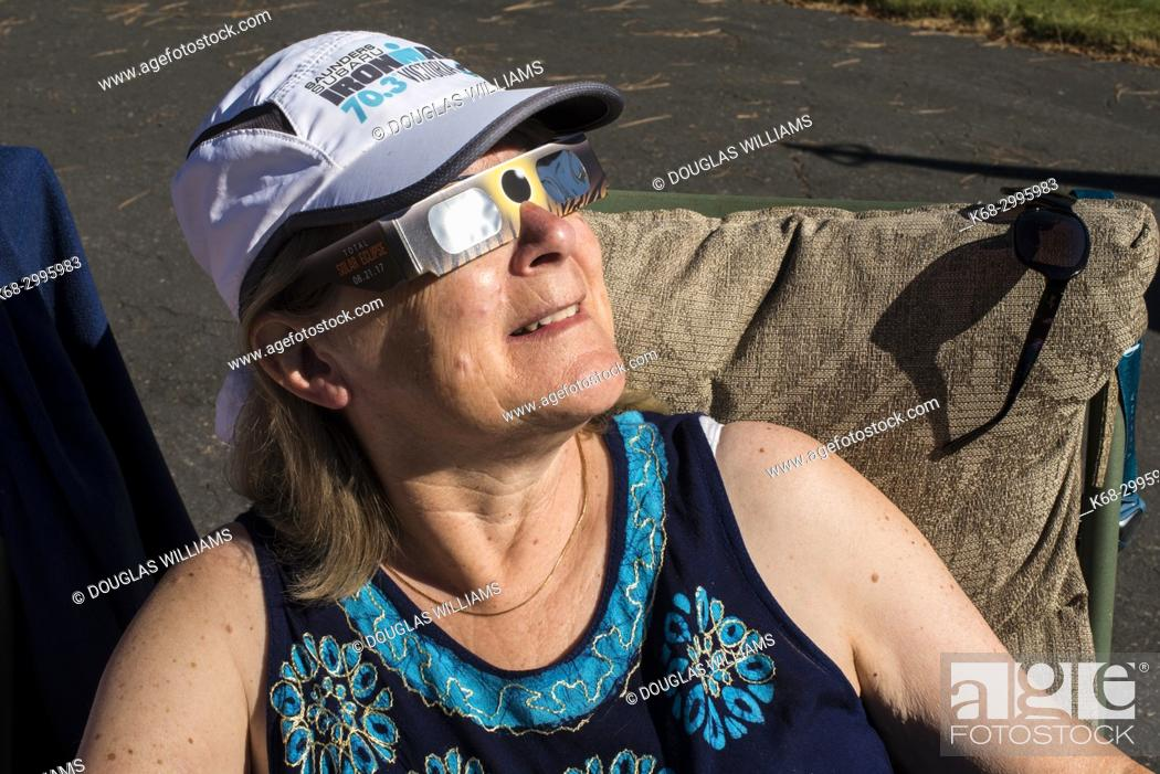 Imagen: Woman looking at solar eclipse with protective glasses.
