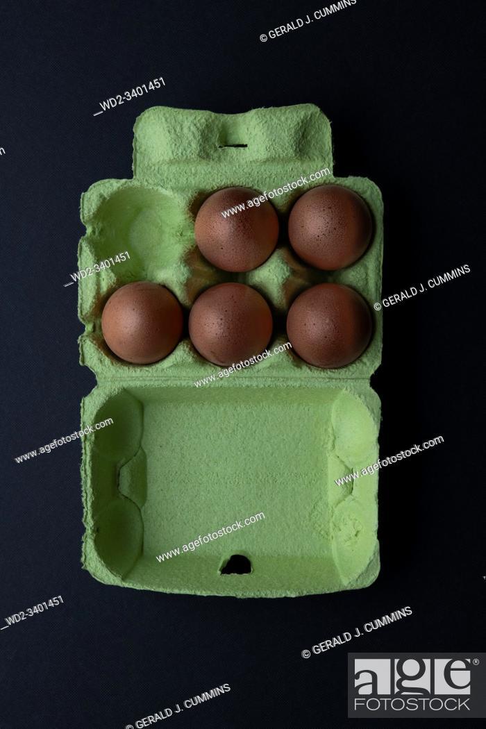 Stock Photo: Five Brown eggs in a green cardboard carton. Dark Background.