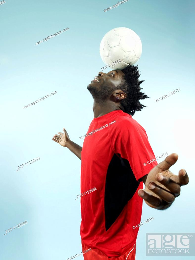 Stock Photo: A young man balancing a soccer ball on her forehead.