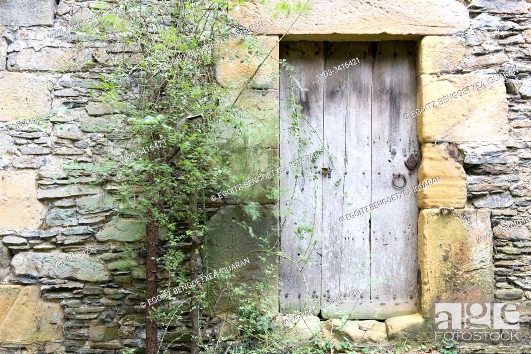 Stock Photo: Old wooden door and stone wall. Agorregi, Pagoeta Natural Park, Basque Country, Spain.