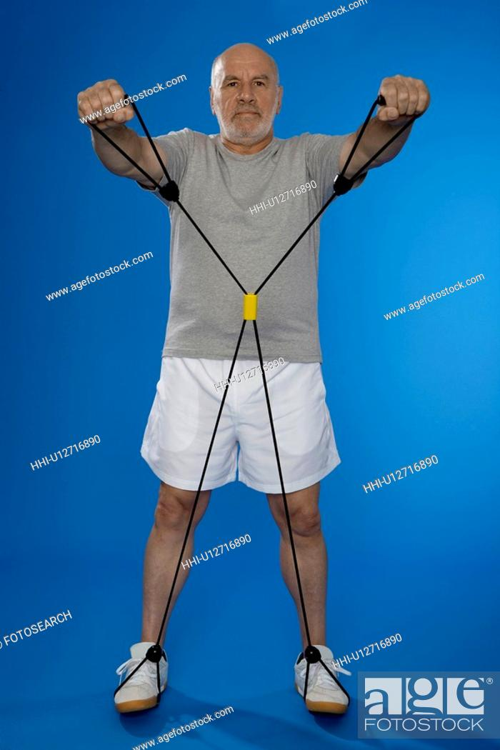 Stock Photo: Senior man exercising with resistance band.