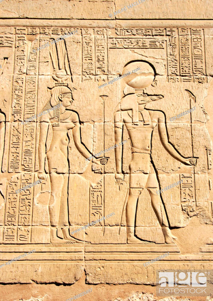 Stock Photo: Reliefs of Sobek with crocodile head and Isis surrounded by hieroglyphs in the Crocodile temple in Kom Ombo: the temple was built in honnor of Sobek and Horus.