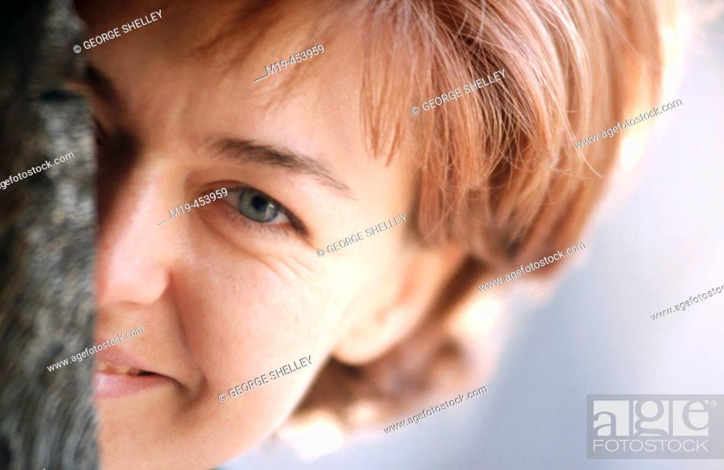 Stock Photo: woman peeking from behind a tree.