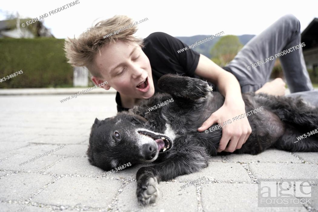 Imagen: Teenager playing with his dog, in Gaissach, Bavaria, Germany.