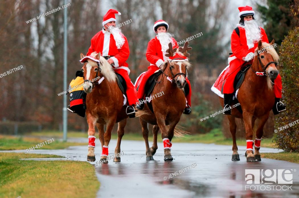 Stock Photo: Equestrians dressed as Santas distribute Christmas gifts to seniors with an illuminated and decorated carriage on the island of Ummanz off the west coast of the.