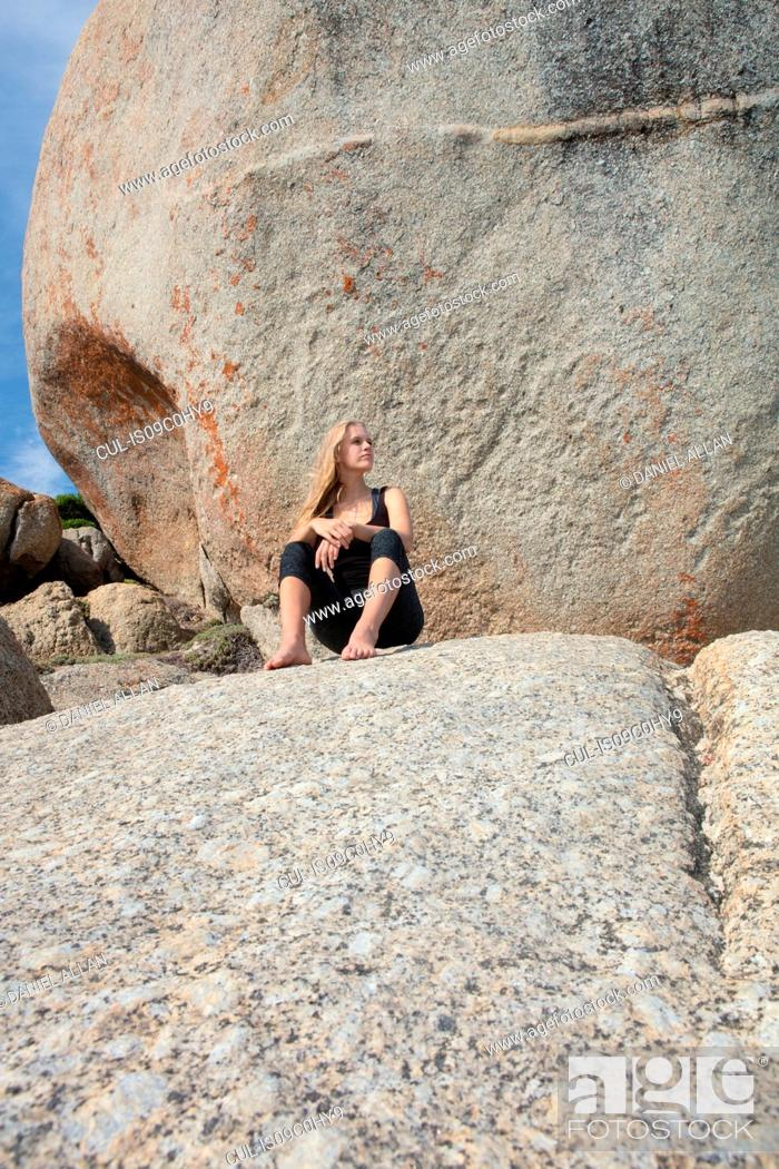 Stock Photo: Young woman practicing yoga taking a break on beach boulder, Cape Town, Western Cape, South Africa.