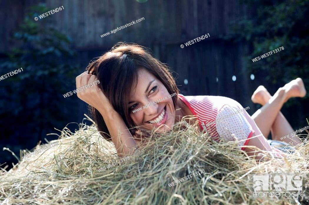 Stock Photo: Germany, Bavaria, Woman lying on haystack, smiling, portrait.