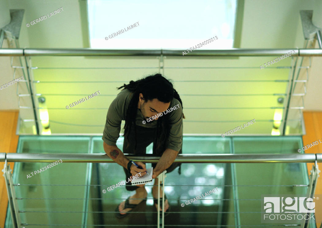 Stock Photo: Man leaning on rail, writing, high angle view.