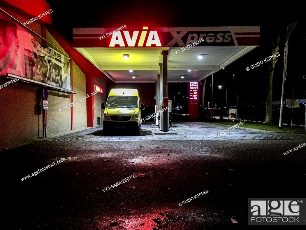 Stock Photo: Tilburg, Netherlands. Local Gas & Fuel Station Servicing a Taxi Bus at Night.