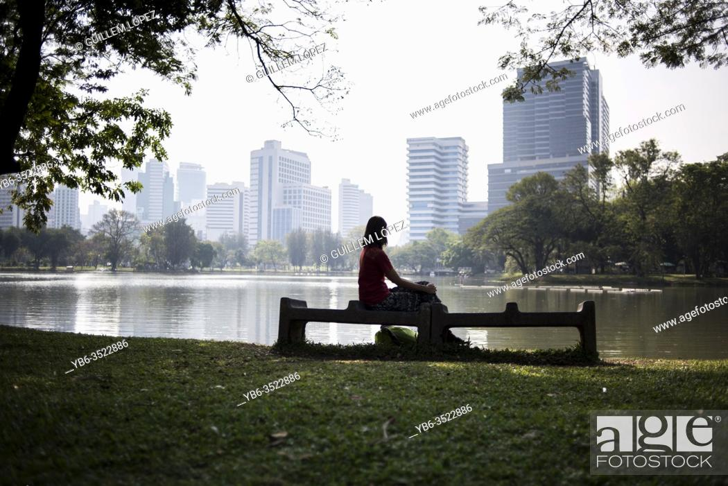 Stock Photo: A young woman rests in a bench of the Lumpini Park in Bangkok, Thailand.