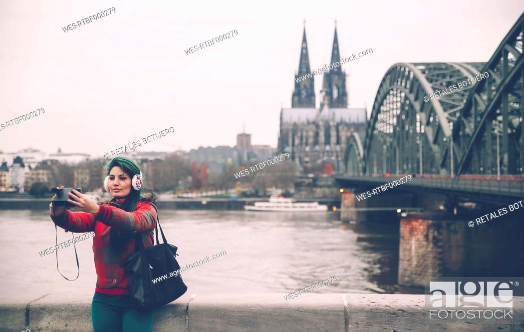 Photo de stock: Germany, Cologne, woman with ear muff taking selfie with polaroid camera.