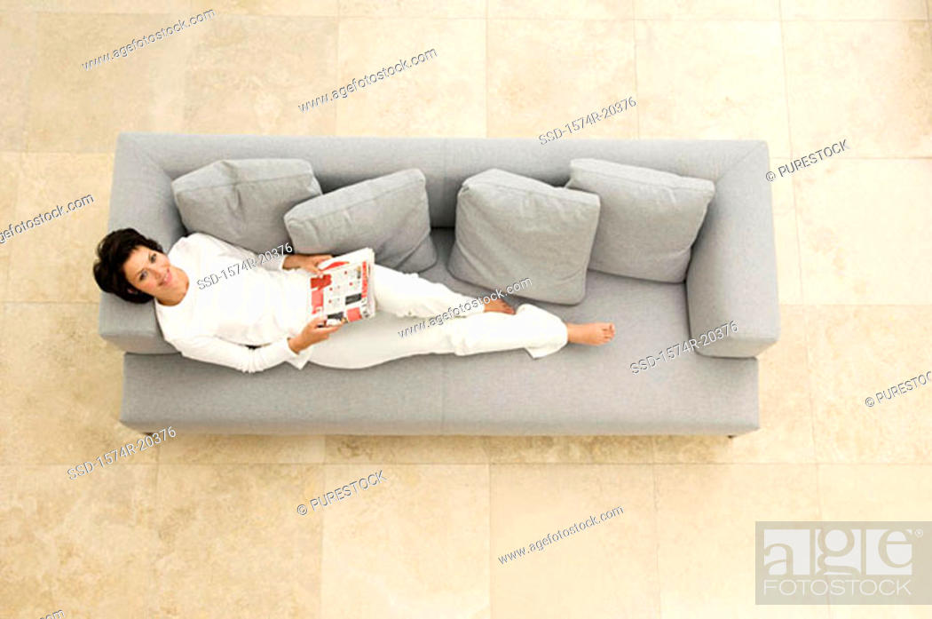 Stock Photo: Portrait of a young woman lying on a couch.