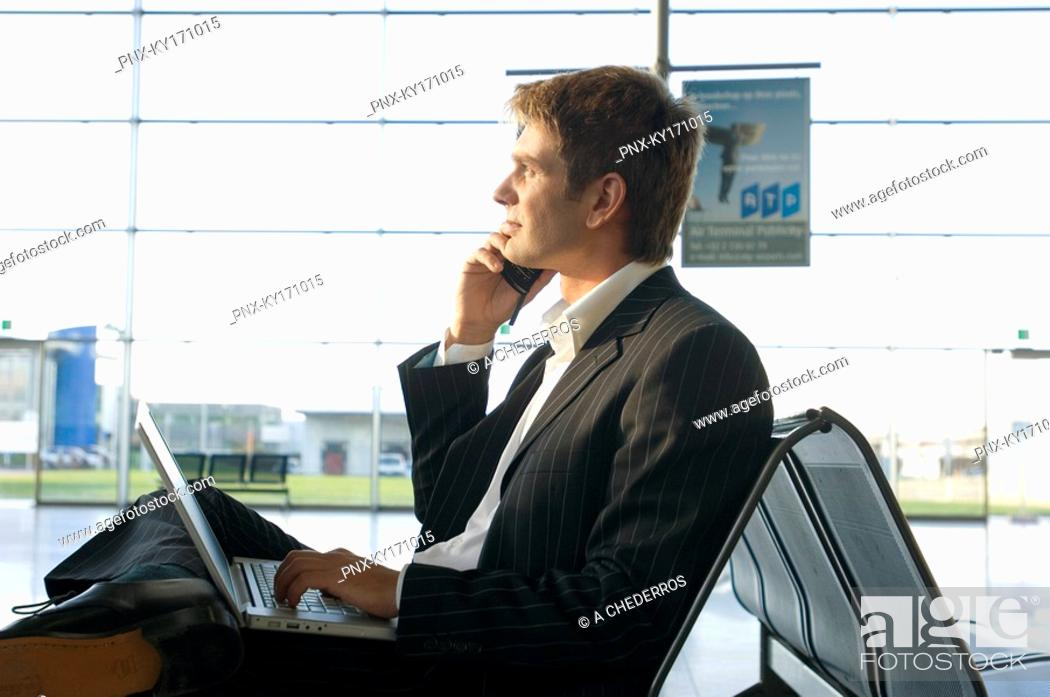 Stock Photo: Side profile of a businessman using a laptop and talking on a mobile phone at an airport lounge.