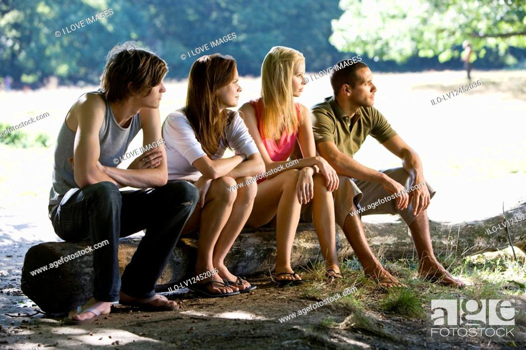 Stock Photo: Four people sitting on a log, looking away.