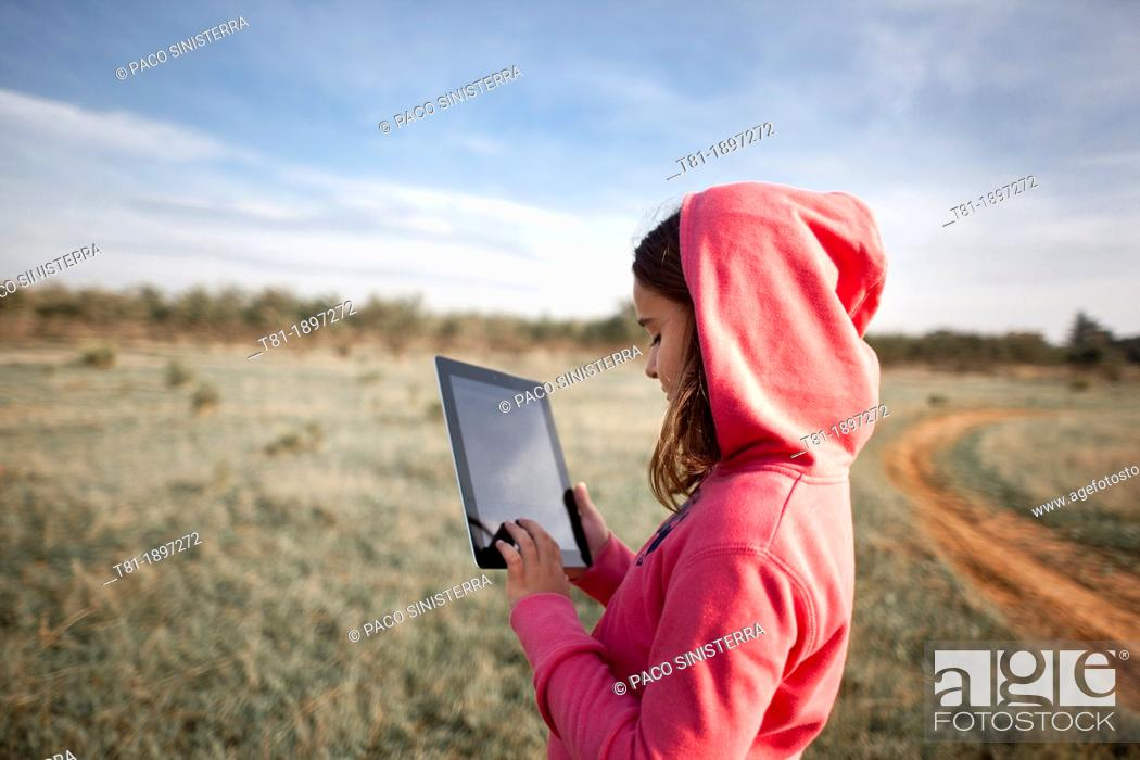 Stock Photo: girl in the field with tablet.