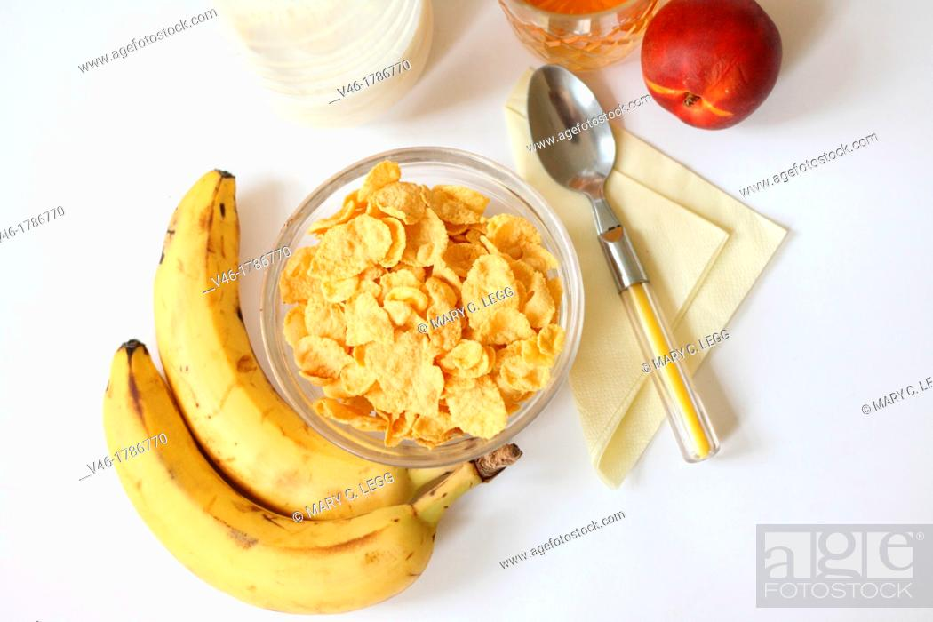 Stock Photo: Breakfast cornflakes with milk and fruit  Cornflakes with bananas for healthy breakfast  Juice in lead glass  Nectarine  Yellow napkin with yellow flatware.