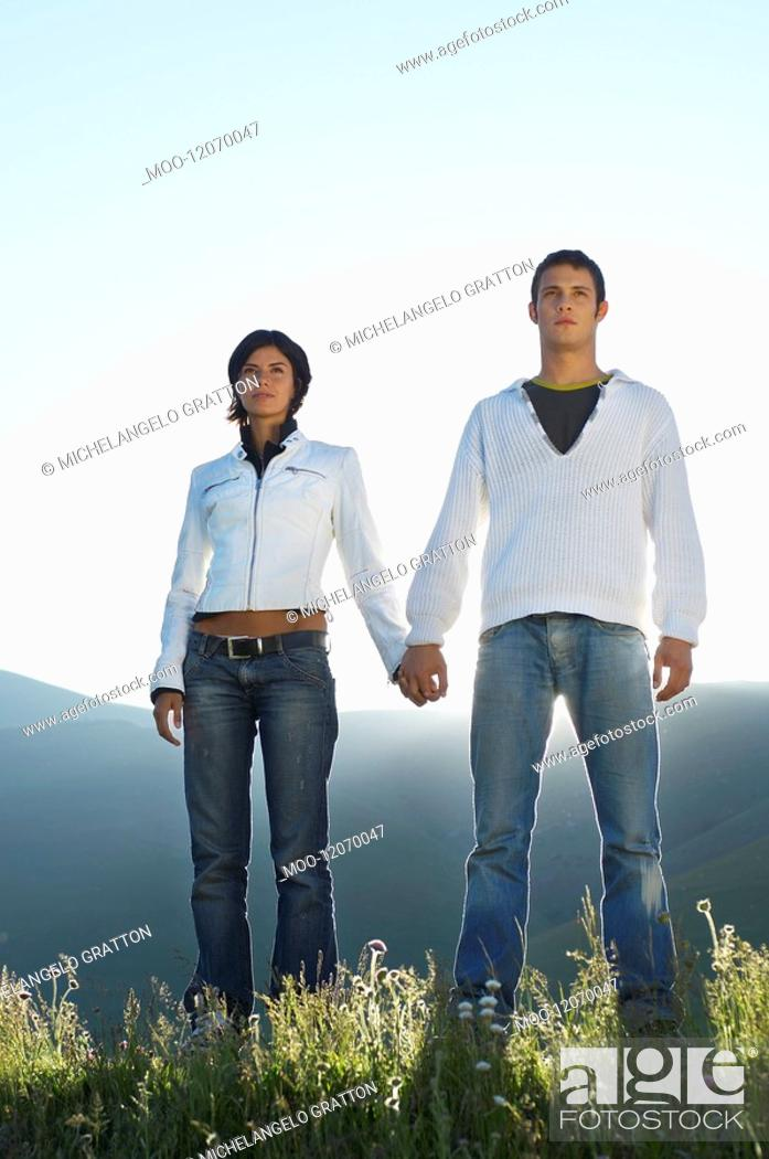 Stock Photo: Young couple standing in mountain field looking at view front view low angle view.