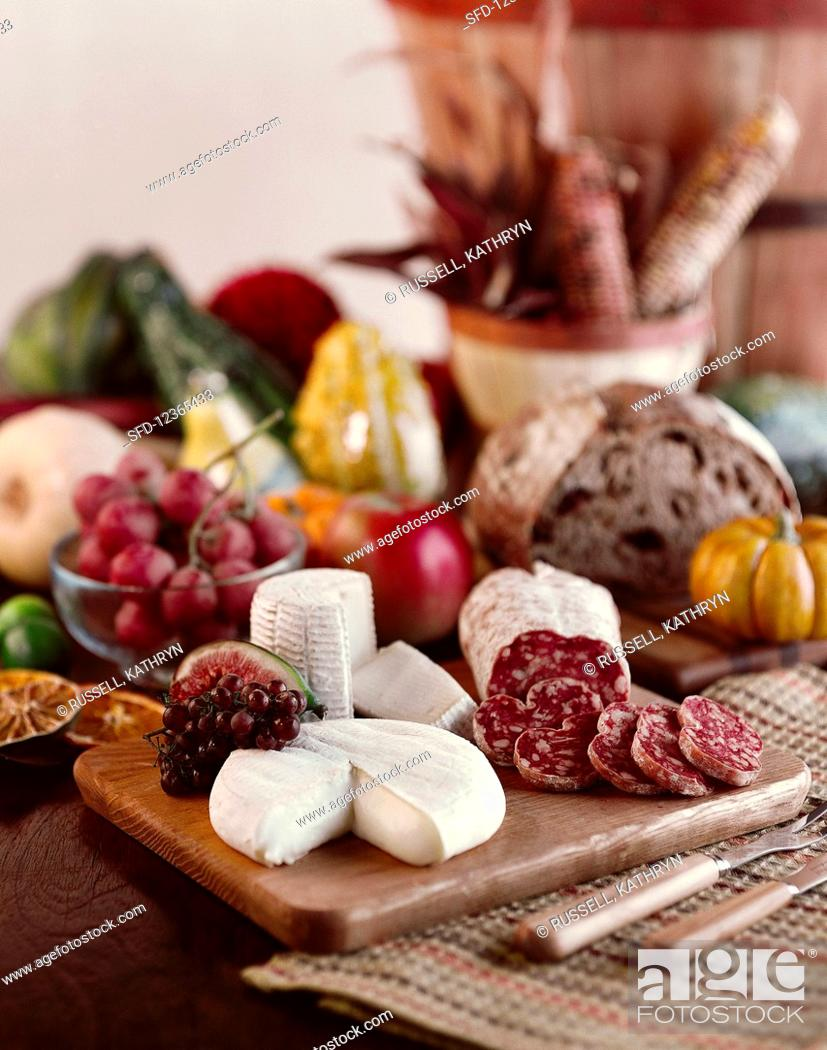 Stock Photo: Still life with salami, cheese, autumn fruits and pumpkins.