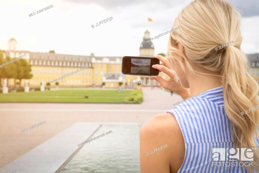 Stock Photo: Germany, Karlsruhe, tourist taking picture of castle.