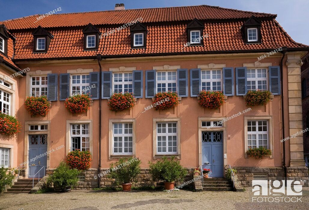 Stock Photo: White with gray trim windows on old architectural style building decorated with flower boxes of red geraniums, Speyer, Germany.