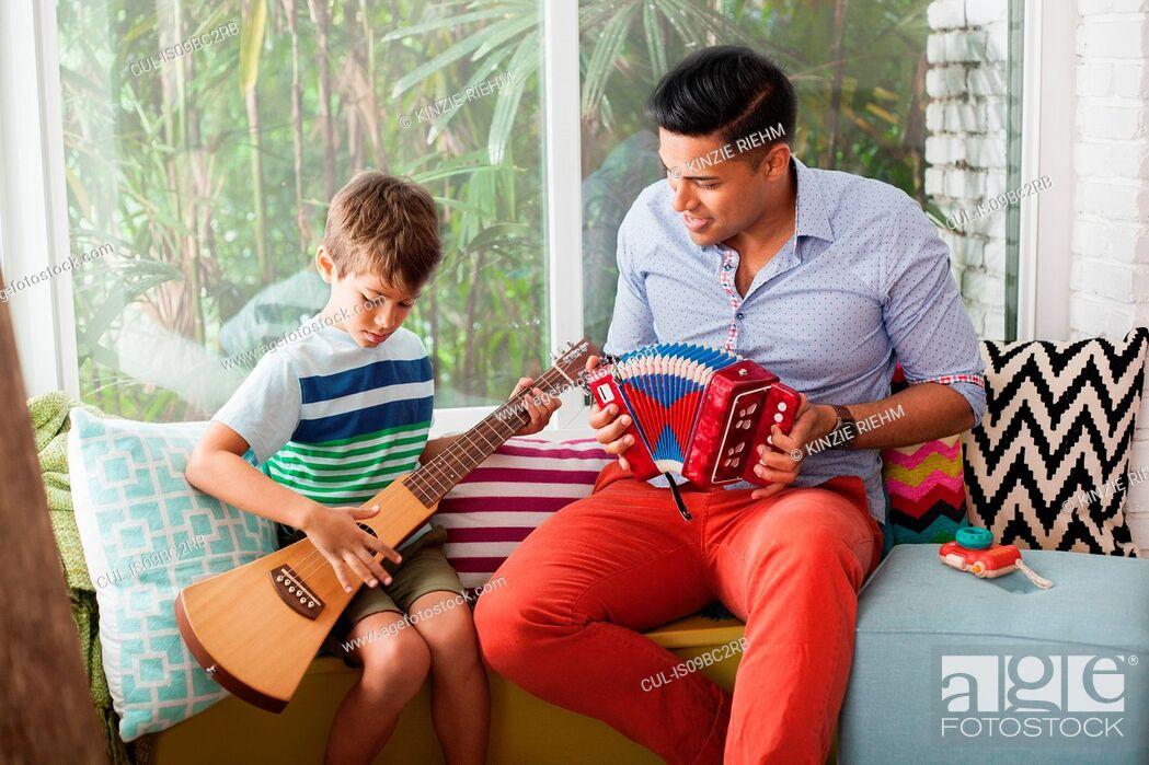 Imagen: Boy playing guitar with music teacher on window seat.