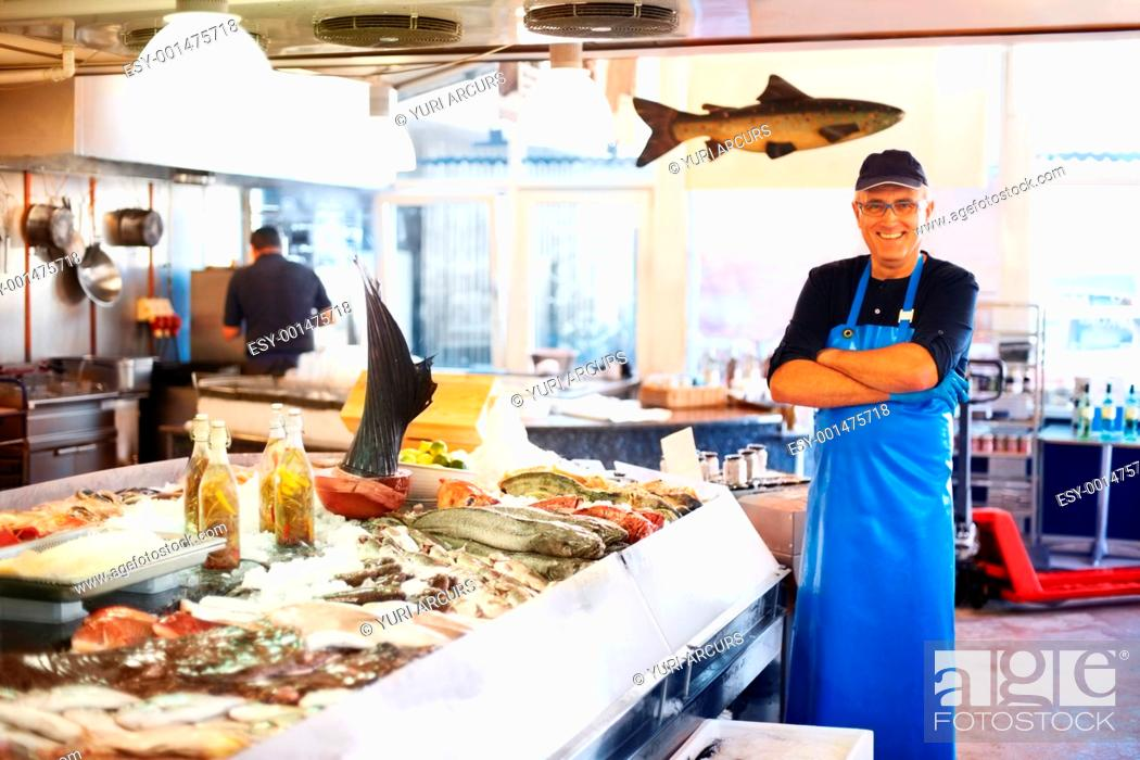 Photo de stock: Happy fishmonger standing in market with his arms folded.