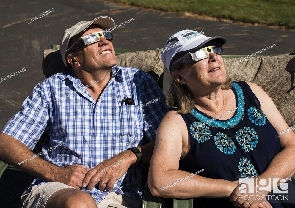 Imagen: Couple looking at solar eclipse with protective glasses.