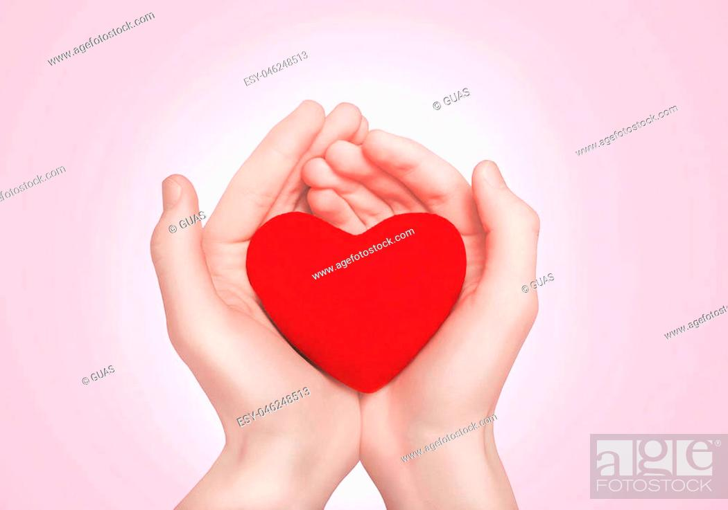 Stock Photo: Open hands holding showing red heart over pink background.