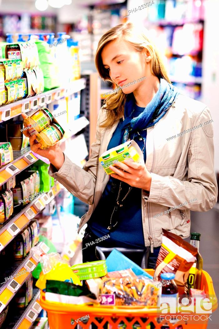 Stock Photo: Woman shopping in baby food section in supermarket.