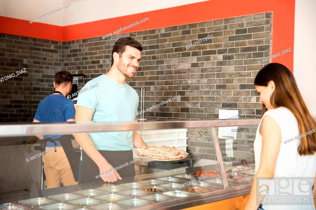 Stock Photo: Handsome young chef preparing pizza as per customer choice behind counter in pizzeria.