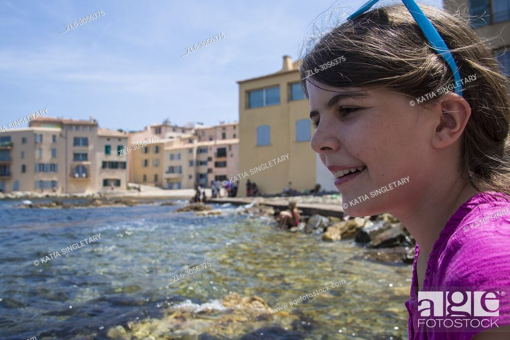 Stock Photo: A preteen all dress in pink playing on the side of the bay of Saint Tropez. We can see the city village of Saint Tropez in France behind her.
