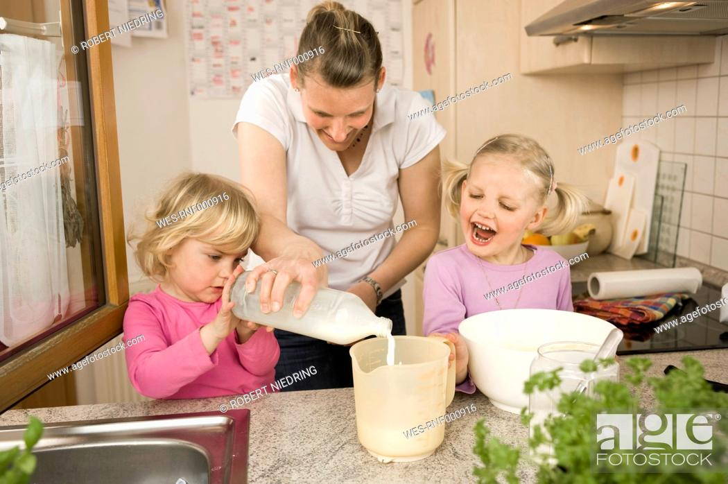 Stock Photo: Mother and daughter pouring milk into measuring cup.