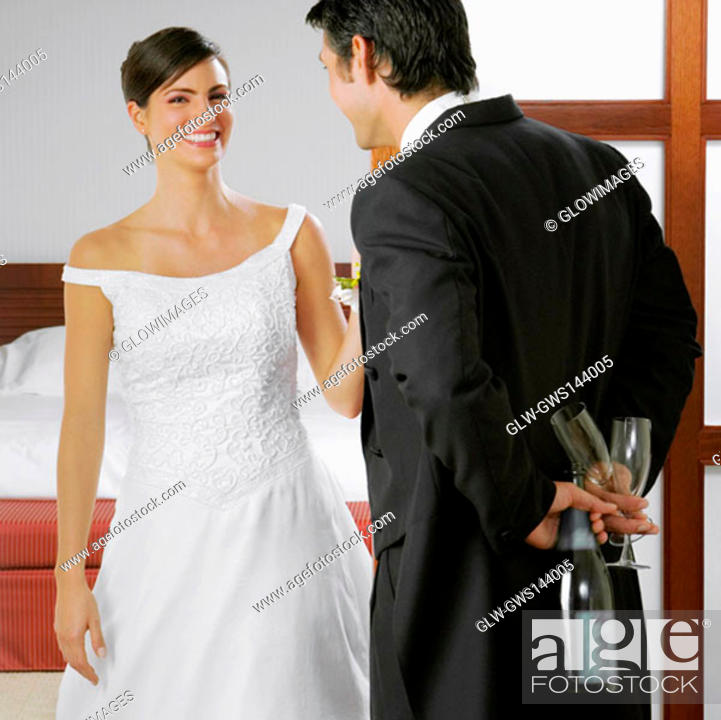 Stock Photo: Groom looking at his bride and holding a bottle and glasses behind his back.