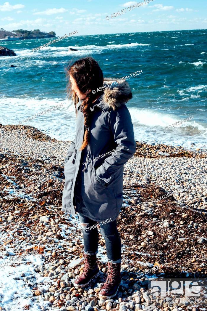 Stock Photo: Full length view of woman on shingle beach wearing winter coat looking away.
