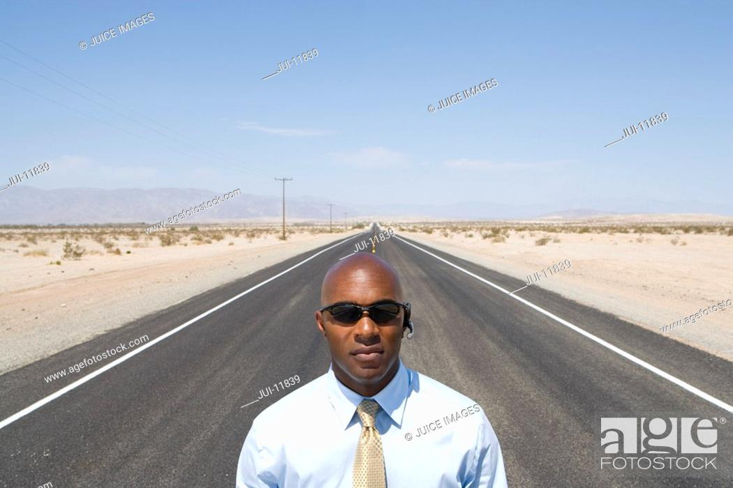 Stock Photo: Businessman in sunglasses in middle of road in desert, elevated view.