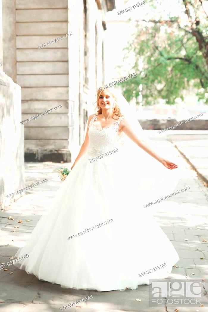 Stock Photo: Beautiful bride spinning with perfect dress in the park.