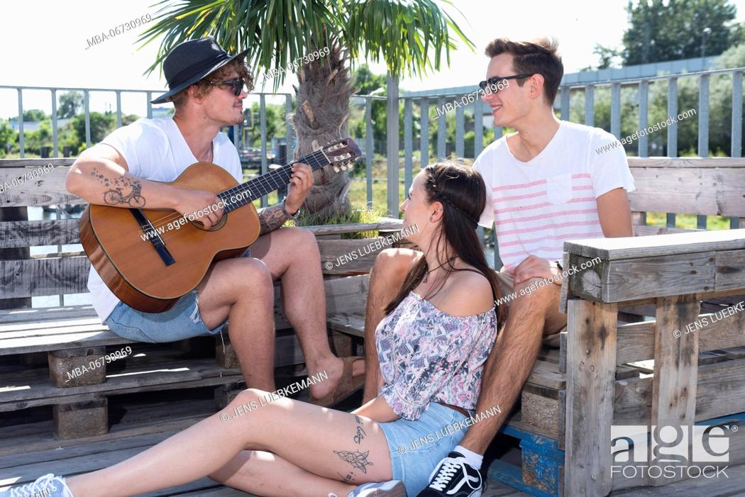 Imagen: Two young men and a girl outside close guitar.