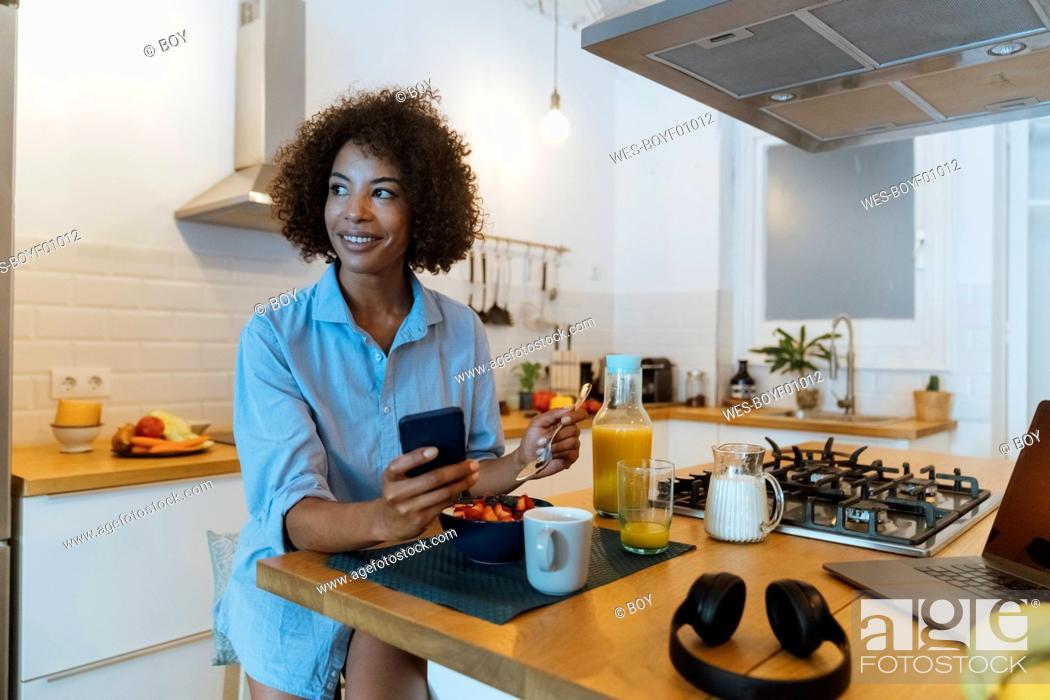 Stock Photo: Woman having breakfast in her kitchen, using smartphone.