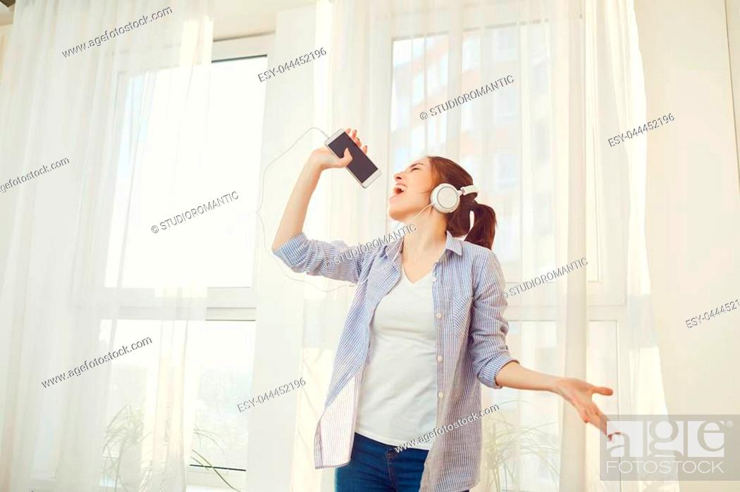 Stock Photo: A girl in headphones sings a song against the window in the morning.
