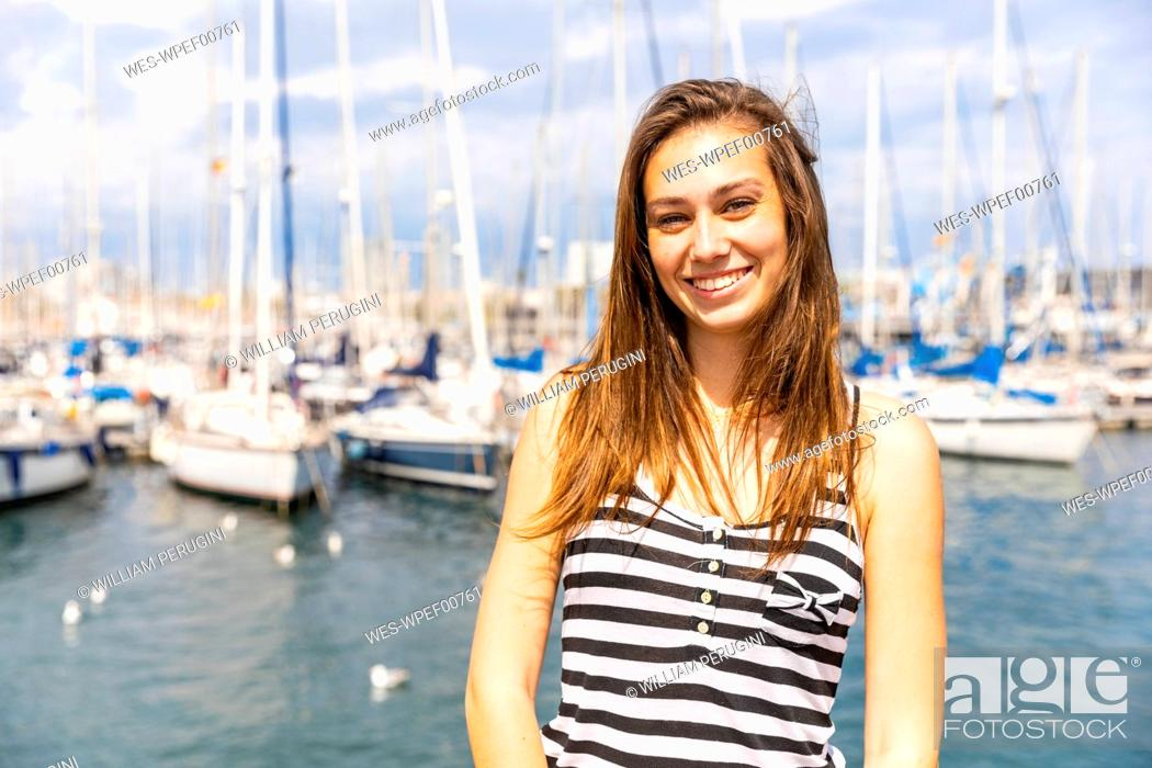 Stock Photo: Portrait of smiling young woman at a marina.