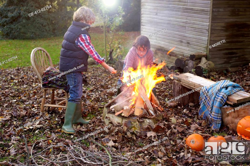 Stock Photo: Children building bonfire outdoors.