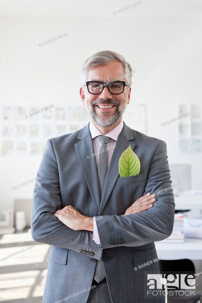 Stock Photo: Portrait of smiling businessman with green leaf in his jacket pocket.