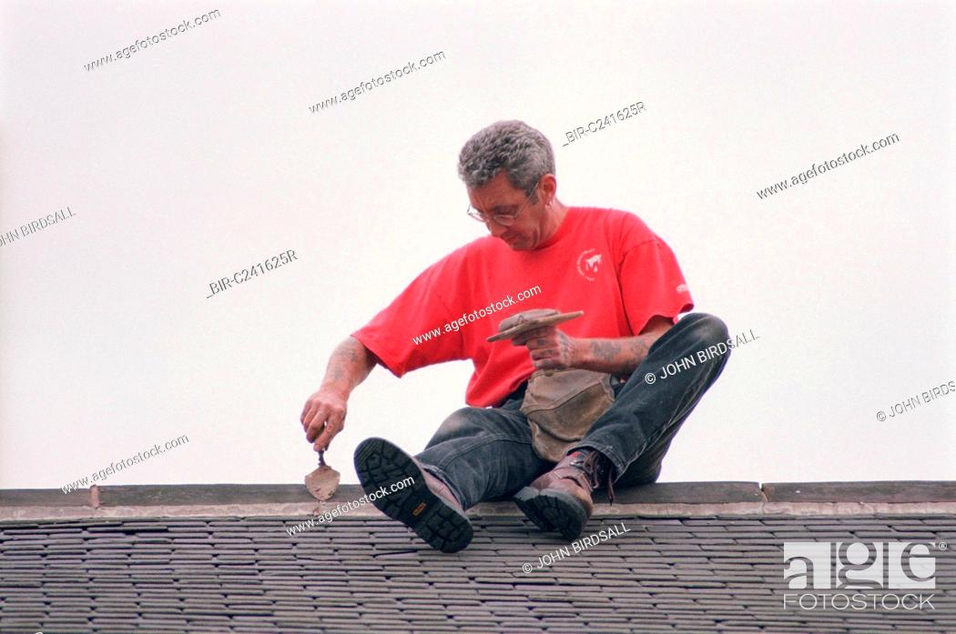 Builder Sitting On Roof Using Mortar To Repoint Ridge Tiles Stock Photo Picture And Rights Managed Image Pic Bir C241625r Agefotostock